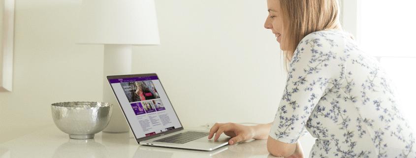 Raskaana oleva nainen käyttää kannettavaa tietokonetta